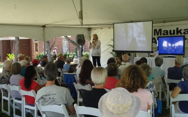 author Susan Scott on stage and back of people in audience