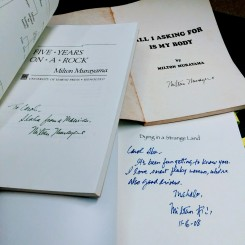 3 books opened to page showing author signed the book